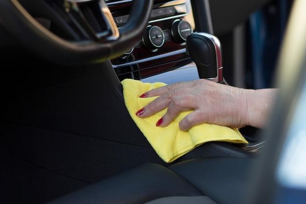Dojrzała kobieta ręka z ściereczką z mikrofibry do czyszczenia wewnętrznego panelu pojazdu myjnia samochodowa komercyjna