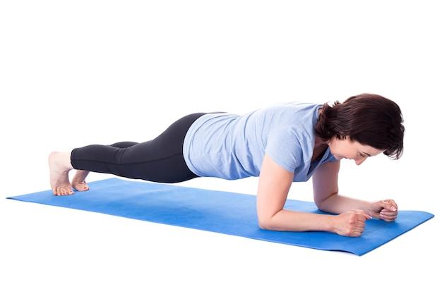 Dojrzała kobieta robi ćwiczenia na macie do jogi na białym tle