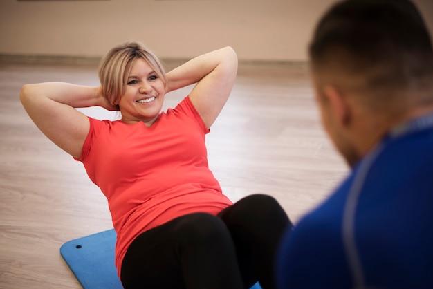 Dojrzała kobieta robi ćwiczeniu z trenerem