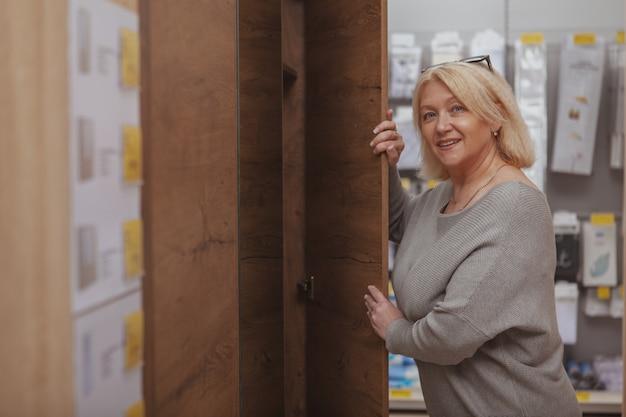 Dojrzała kobieta robi zakupy przy meblarskim sklepem