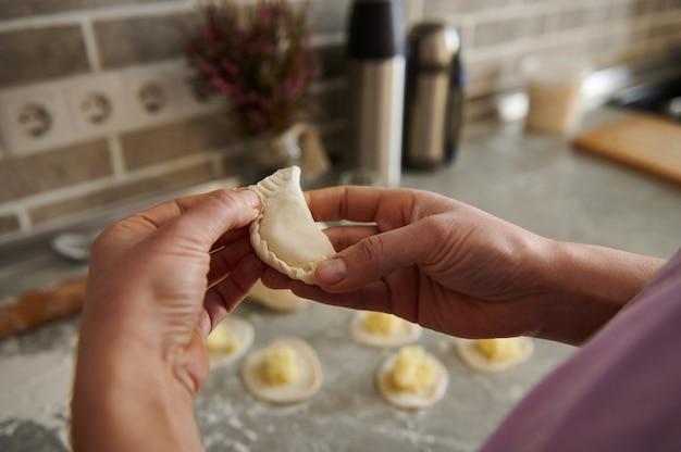 Dojrzała kobieta robiąca tradycyjne pierogi (vareniki lub ravioli)