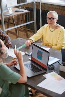 Dojrzała kobieta rozmawia z koleżanką podczas pracy na komputerze podczas spotkania w biurze