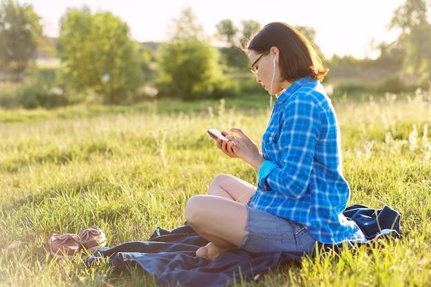 Dojrzała kobieta słucha muzyki, audiobooka na słuchawkach, relaksuje się na łonie natury. zachód słońca w tle, rustykalne krajobrazy, zielona łąka, kopia przestrzeń