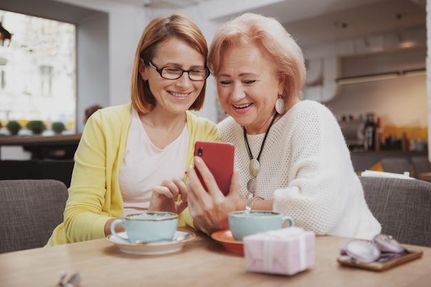 Dojrzała kobieta spotyka jej starszej matki przy sklep z kawą