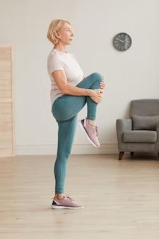 Dojrzała kobieta stojąc i rozciągając nogę podczas ćwiczeń w domu
