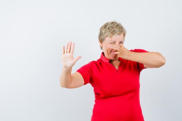 Dojrzała kobieta szczypie nos z powodu nieprzyjemnego zapachu w czerwonej koszulce i wygląda na zniesmaczoną.