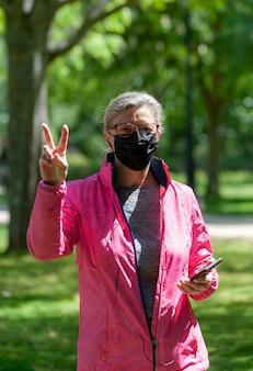 Dojrzała kobieta trenuje spacerując po parku, czyniąc palcami symbol zwycięstwa