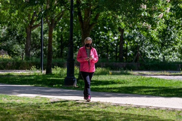 Dojrzała kobieta trenuje spacerując po parku, jednocześnie konsultując się z sieciami społecznościowymi na swoim telefonie komórkowym