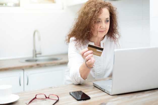 Dojrzała kobieta trzyma kartę kredytową i używa laptopa w domu. zakupy online, handel elektroniczny i bankowość internetowa z koncepcji domu.