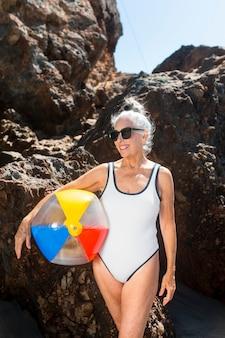 Dojrzała kobieta trzyma piłkę plażową w stroju kąpielowym