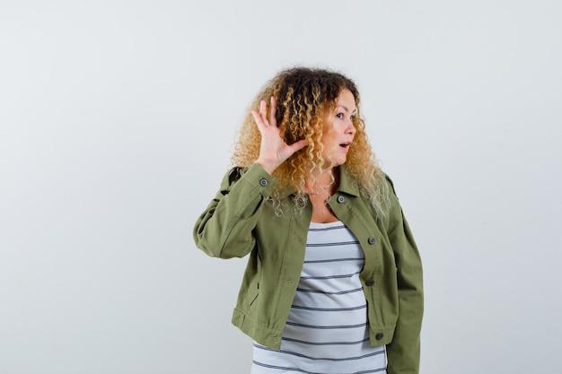 Dojrzała kobieta trzymająca dłoń za uchem, aby usłyszeć, otwiera usta w zielonej kurtce, t-shircie i wygląda na zaskoczoną. przedni widok.