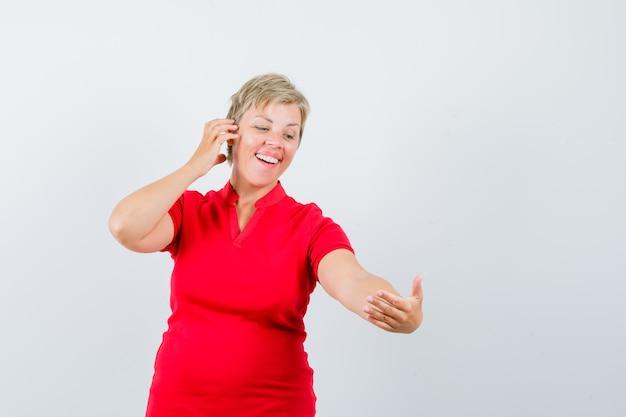 Dojrzała kobieta udająca rozmowę wideo w czerwonej koszulce i rozbrykana.