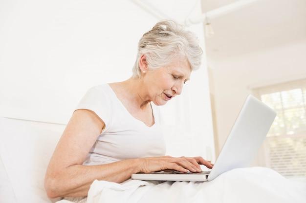 Dojrzała kobieta używa laptopu obsiadanie na łóżku