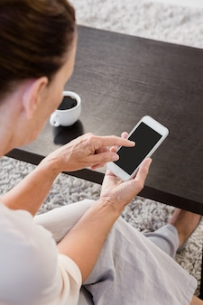 Dojrzała kobieta używa smartphone