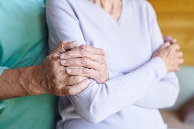 Dojrzała kobieta w casual, trzymając się za ręce kochającego męża, obejmując ją, jednocześnie relaksując się w domu