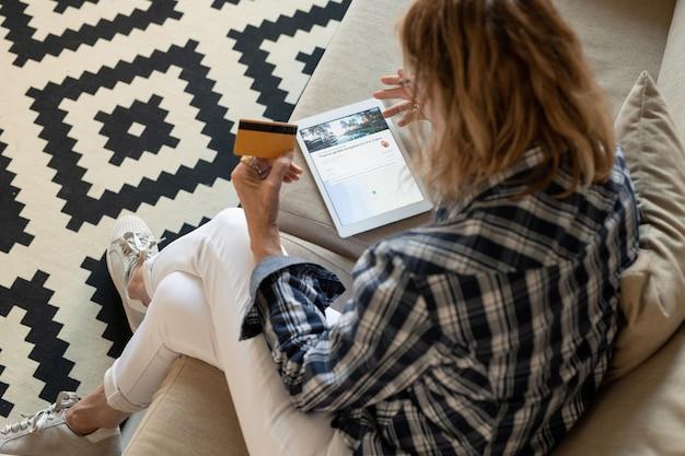 Dojrzała kobieta w codziennym stroju siedzi na kanapie w domu i zamierza kupić wycieczkę wakacyjną kartą kredytową, przeglądając oferty online
