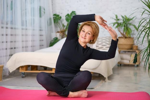 Dojrzała kobieta w czarnym dresie robi joga siedzi na macie w domu, na tle łóżka i doniczek z zielonymi roślinami, koncepcja zdrowego stylu życia siedzi w domu