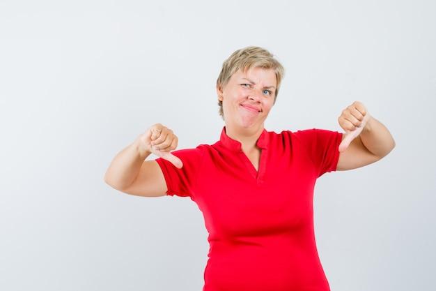 Dojrzała kobieta w czerwonej koszulce pokazuje podwójny kciuk w dół i wygląda na niezadowoloną