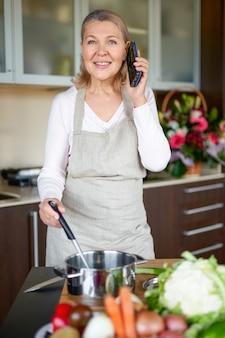 Dojrzała kobieta w kuchni przygotowuje jedzenie i trzyma inteligentny telefon