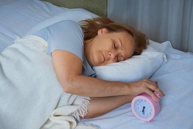 Dojrzała kobieta w niebieskiej piżamie rano wyłącza budzik w swoim łóżku