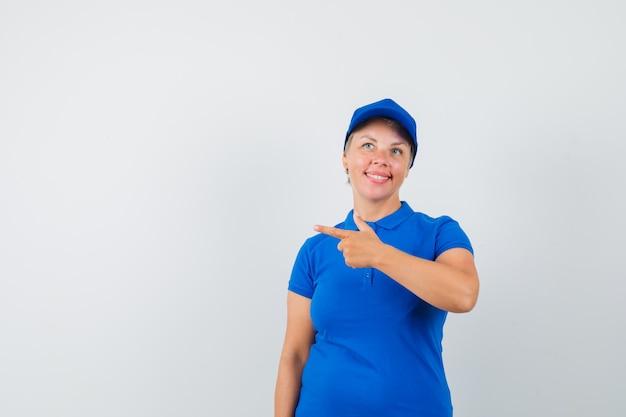 Dojrzała kobieta w niebieskim t-shircie skierowana w lewą stronę i wyglądająca wesoło.