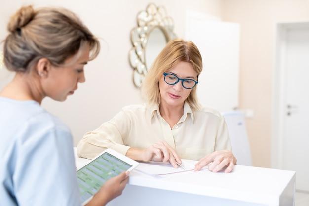 Dojrzała kobieta w okularach podczas wypełniania jej w gabinecie pyta administratora o treść umowy
