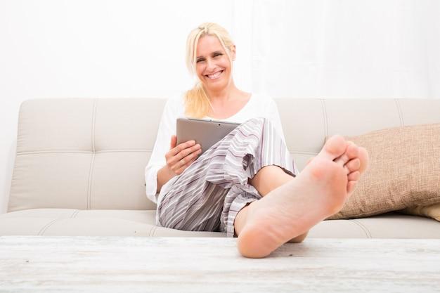 Dojrzała kobieta w piżamie z tabletem na kanapie.