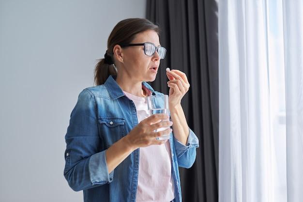 Dojrzała kobieta w średnim wieku w ubranie w domu trzymając pigułkę i szklankę świeżej wody. bóle głowy, depresja, preparaty witaminowe, uspokajające, menopauza