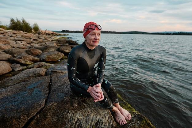 Dojrzała kobieta w stroju kąpielowym siedzi na skale po kąpieli w jeziorze