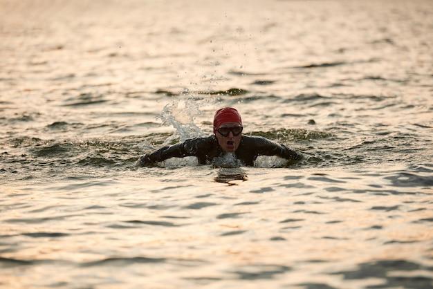 Dojrzała kobieta w stroju kąpielowym trenuje pływanie w jeziorze na świeżym powietrzu
