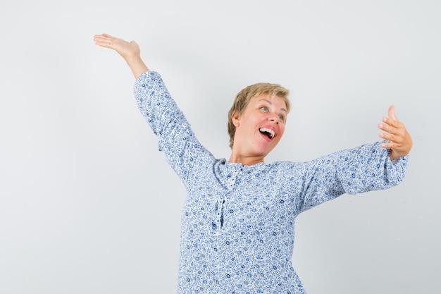 Dojrzała kobieta w sukience, rozkładając uniesione ramiona i wyglądająca błogo