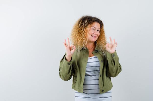 Dojrzała kobieta w zielonej kurtce, t-shirt z oznakami ok i wyglądająca na zadowoloną, widok z przodu.