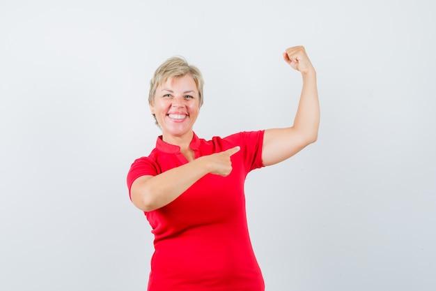 Dojrzała kobieta, wskazując na mięśnie ramion w czerwonej koszulce i patrząc pewnie