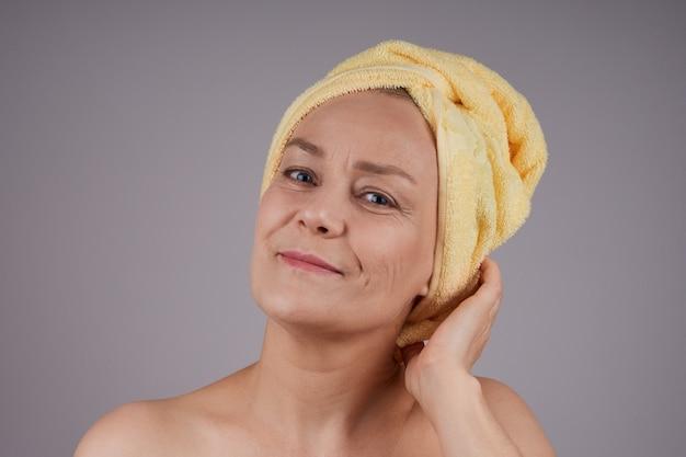 Dojrzała kobieta z odkrytymi ramionami z ręcznikiem na głowie uśmiechnięta koncepcja pielęgnacji skóry. izoluj na szarej ścianie
