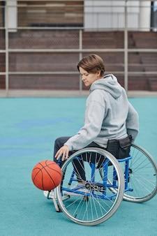 Dojrzała kobieta z paraplegią siedzi na wózku inwalidzkim, grając w koszykówkę na boisku sportowym