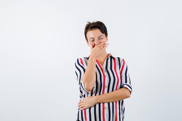 Dojrzała kobieta zakrywająca usta ręką, śmiejąca się, stojąca oczy zamknięte w pasiastej koszuli i wyglądająca wesoło. przedni widok.