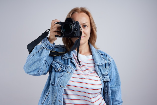 Dojrzała kobieta zawodowy fotograf robi zdjęcie aparatem cyfrowym..