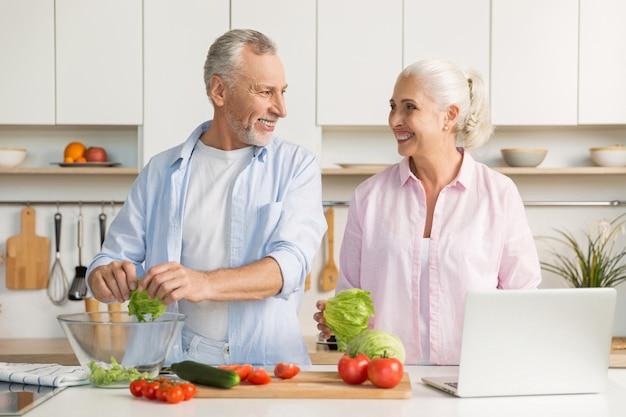 Dojrzała kochająca pary rodzina używa laptop i kulinarną sałatki