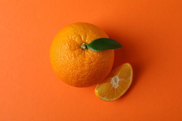 Dojrzała mandarynka z liściem na pomarańczowym tle