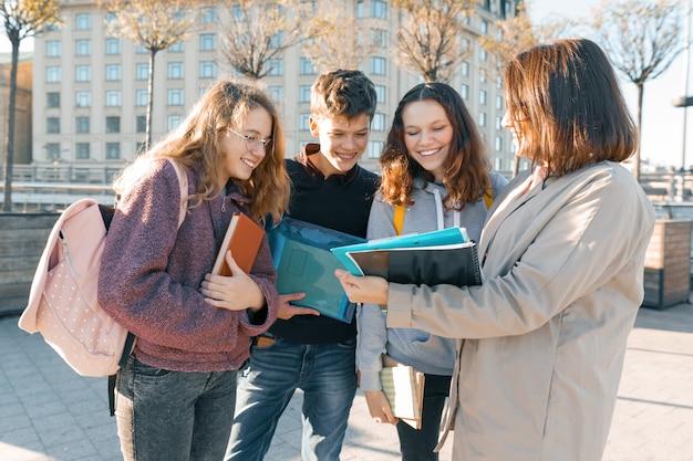 Dojrzała nauczycielka rozmawia z nastoletnimi uczniami