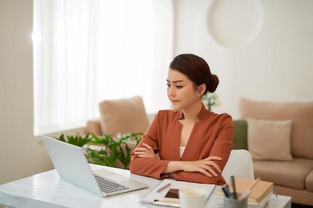 Dojrzała, odnosząca sukcesy kobieta biznesu patrząca na telefon komórkowy w domu w biurze biurowym