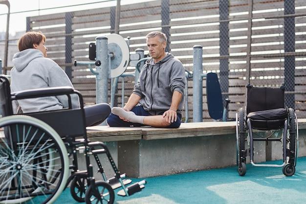 Dojrzała para koleżanek z niepełnosprawnością siedzących na plaży i relaksujących się odpoczywających po zajęciach sportowych...