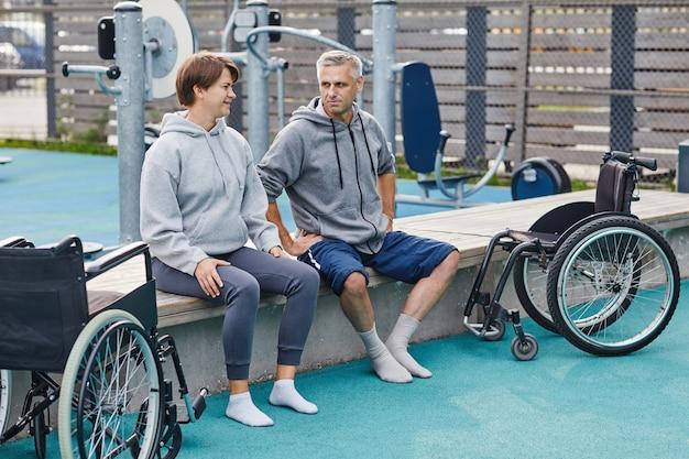 Dojrzała para sprawna siedzi na ławce i rozmawia podczas treningu sportowego na świeżym powietrzu