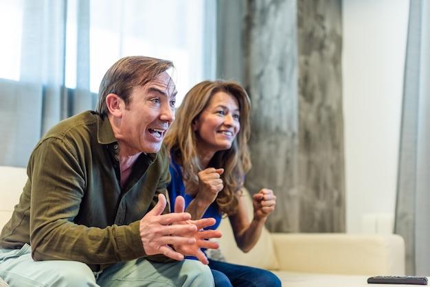 Dojrzała para świętuje coś, co oglądają w telewizji. zdjęcie wysokiej jakości