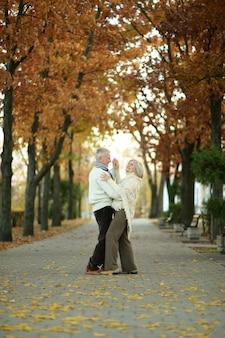Dojrzała para tańczy w jesiennym parku