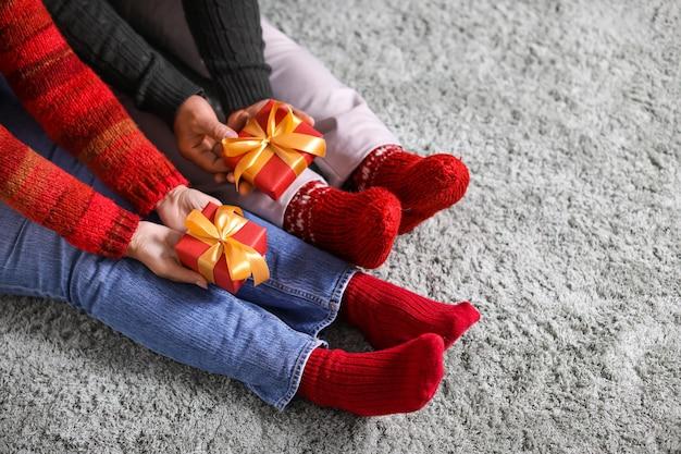 Dojrzała para z prezentami świątecznymi w domu