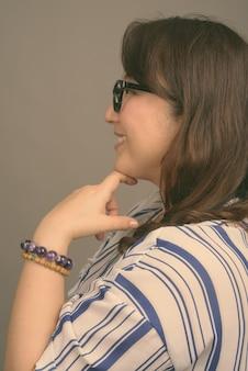 Dojrzała piękna azjatycka bizneswoman nosząca okulary na szaro