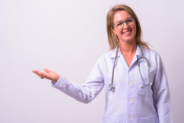 Dojrzała piękna blondynka lekarz przeciw białej przestrzeni