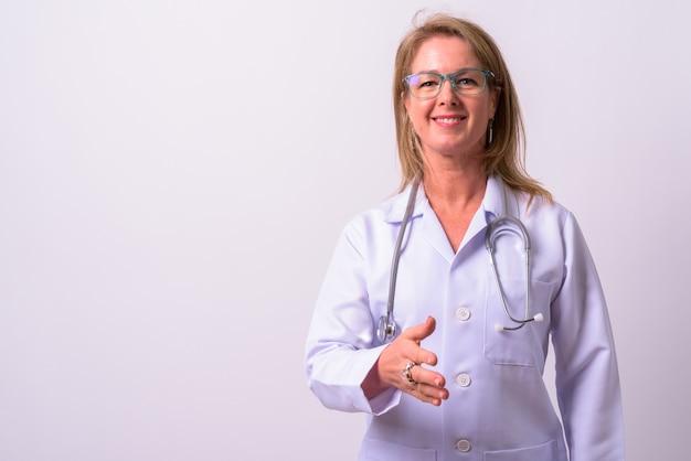 Dojrzała piękna blondynka lekarz przed białą ścianą