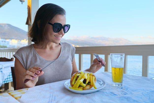 Dojrzała piękna kobieta obiad w kawiarni nadmorskiego kurortu